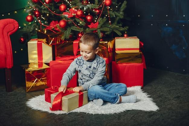 Garotinho sentado perto de árvore de natal Foto gratuita