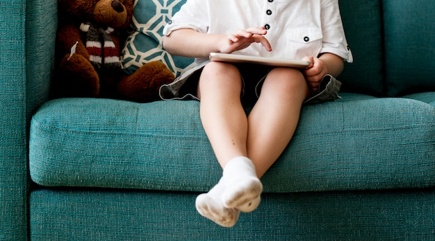 Garotinho sentou-se em um sofá usando tablet digital Foto Premium