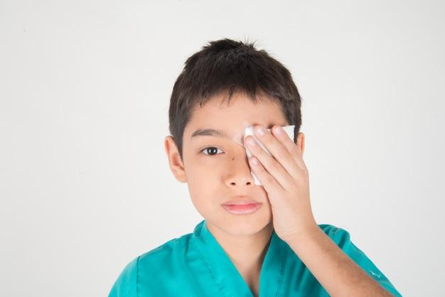 Garotinho tem olhos dor uso curativo para cobrir Foto Premium