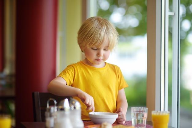 Garotinho tomando café da manhã saudável no restaurante do hotel Foto Premium