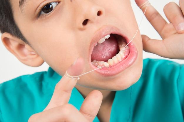 Garotinho usando fio dental para limpar o dente Foto Premium