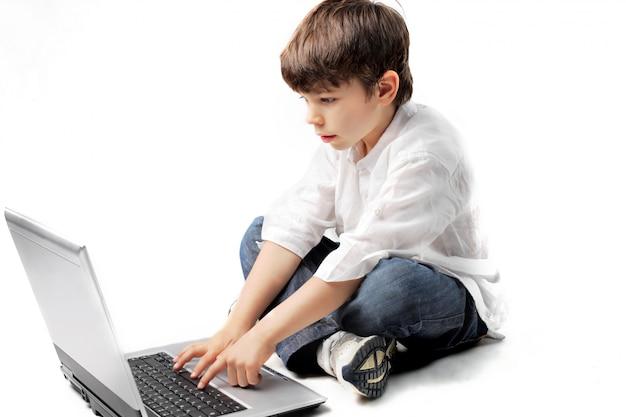 Garotinho usando um laptop Foto Premium