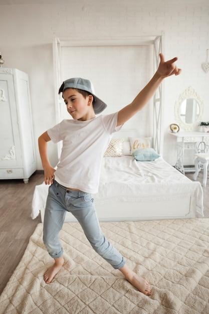 Garotinho vestindo boné e dançando no quarto Foto gratuita