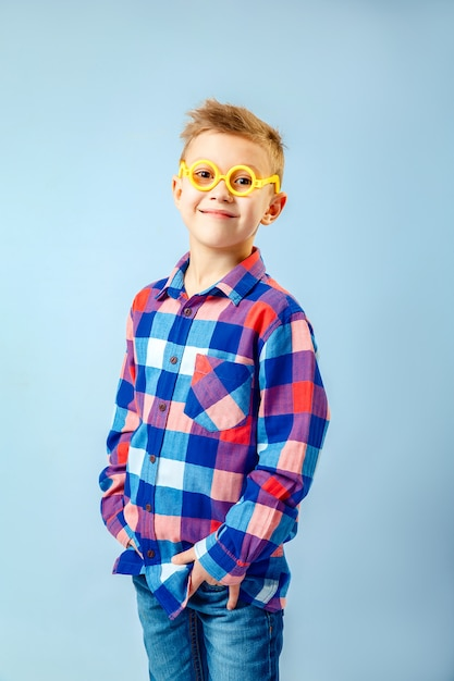 Garotinho, vestindo camisa xadrez colorida, jeans azul, óculos de plástico se divertindo no estúdio Foto Premium