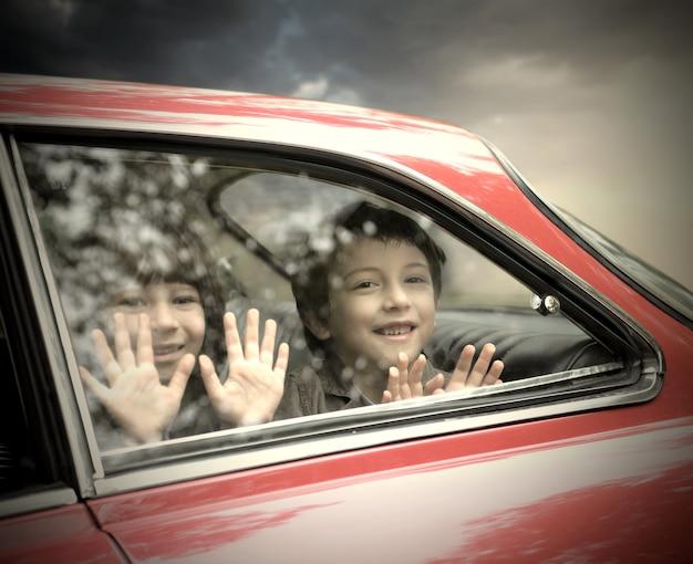 Garotinhos sorrindo de um carro Foto Premium