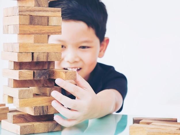 Garoto asiático está jogando jogo de torre de blocos de madeira para praticar a habilidade física e mental Foto gratuita