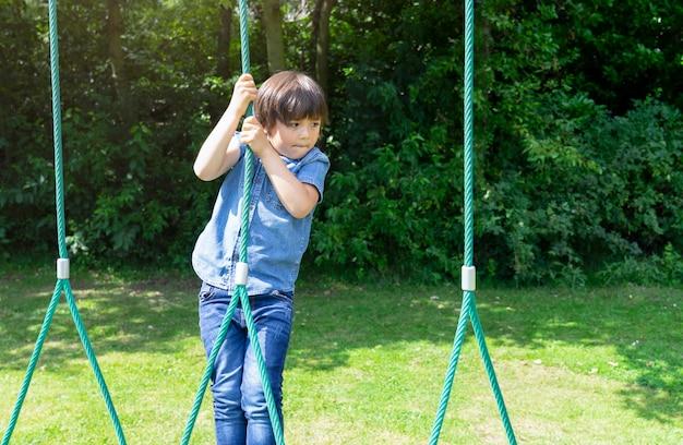 Garoto ativo, segurando o roupão no playground Foto Premium