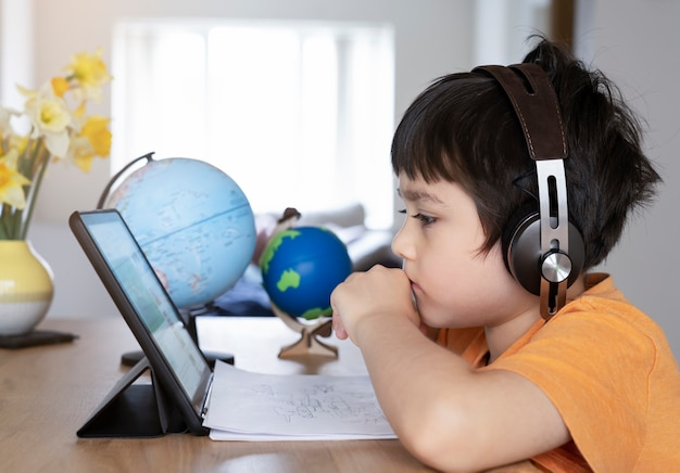 Garoto auto-isolamento usando o tablet para a lição de casa, criança fazendo usando tablet digital, procurando informações na internet Foto Premium