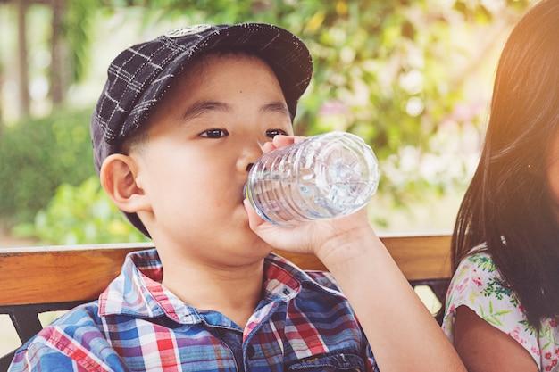Garoto bebe água de uma garrafa Foto Premium
