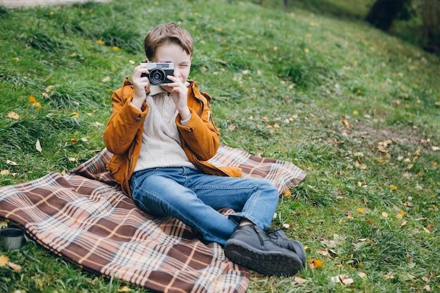 Garoto bonito caminha e posa em um parque colorido de outono Foto Premium
