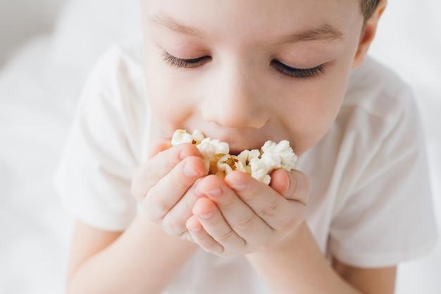 Garoto bonito comendo pipoca sentado na cama com lençóis brancos Foto Premium