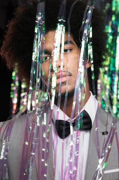 Garoto bonito de terno atrás de uma cortina de festa de ano novo Foto gratuita