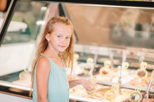 Garoto bonito desfrutando de sorvete italiano real perto de gelateria em roma Foto Premium