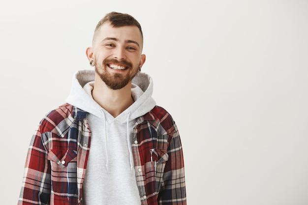 Garoto bonito feliz com barba sorrindo satisfeito Foto gratuita