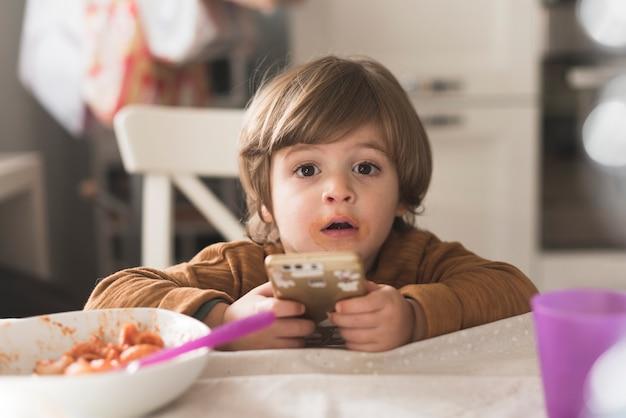 Garoto bonito, segurando o telefone na mesa Foto gratuita