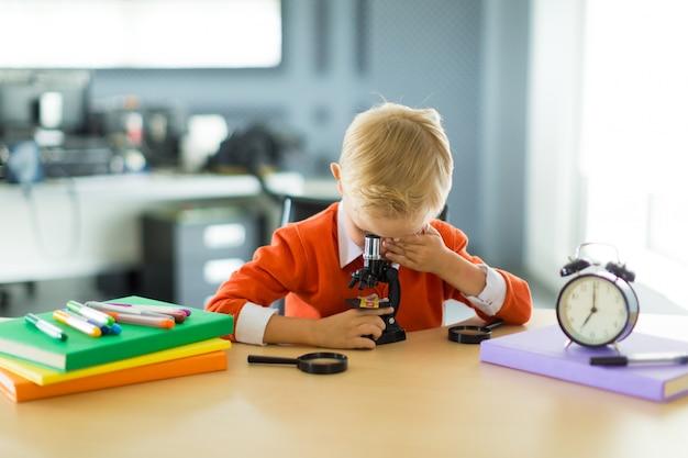 Garoto bonito sentar na mesa do escritório, segure o microscópio Foto Premium