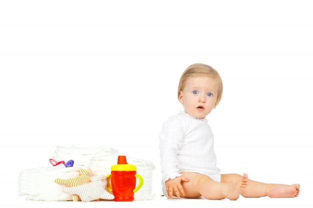 Garoto branco com fraldas empilhadas e brinquedos isolados no branco Foto Premium