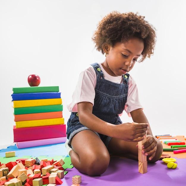 Garoto brincando com cubos no tapete de jogo no estúdio Foto gratuita