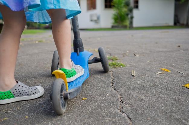Garoto brincando com scooter, atividade para criança, play ground, ao ar livre Foto Premium