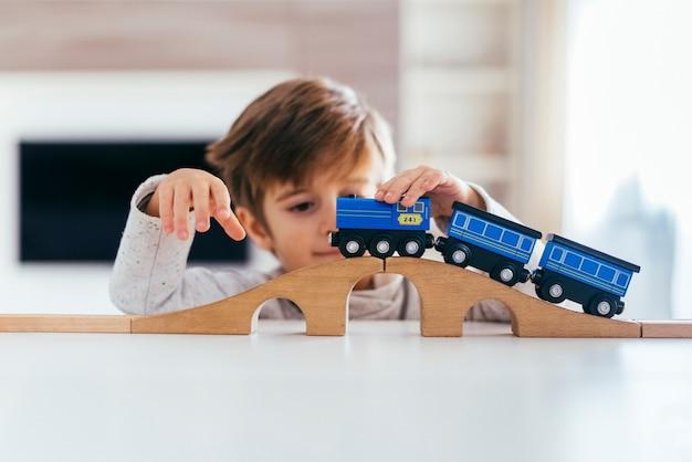 Garoto brincando com trem de brinquedo Foto gratuita