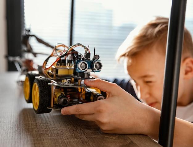 Garoto colocando robô na prateleira Foto gratuita