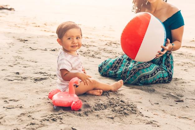 Garoto com a mãe jogando na praia Foto gratuita