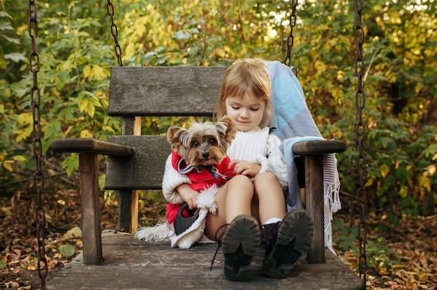Garoto com cachorro engraçado está sentado em uma grande cadeira de madeira no jardim. criança do sexo feminino com cachorrinho posa no quintal. infância feliz Foto Premium
