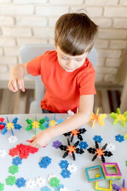 Garoto de alto ângulo com brinquedos florais Foto gratuita