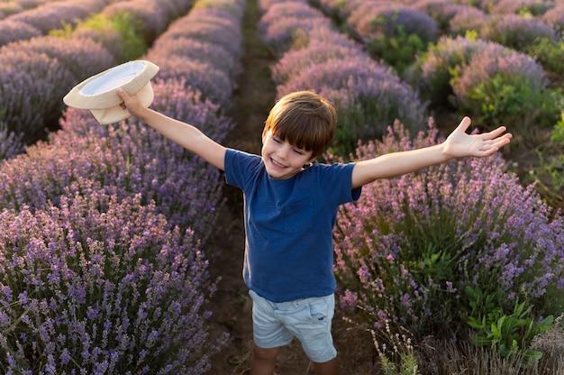 Garoto de alto ângulo no campo de flores Foto gratuita