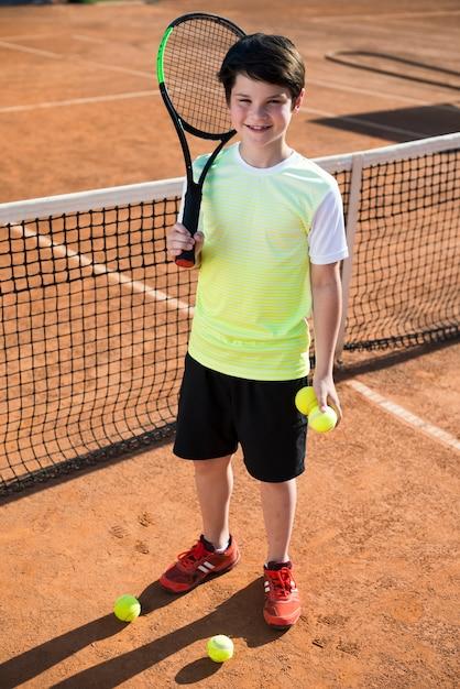 Garoto de alto ângulo no campo de ténis Foto gratuita