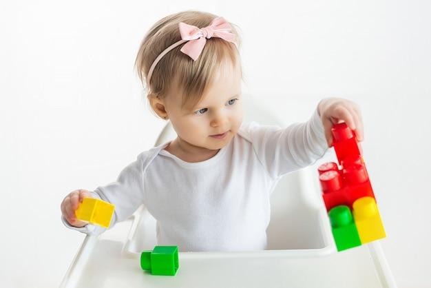 Garoto de berçário brinca com brinquedos educativos em sala de aula, sentado à mesa na cadeira de bebê. menina bonitinha jogando blocos de construção coloridos. fundo branco. Foto Premium