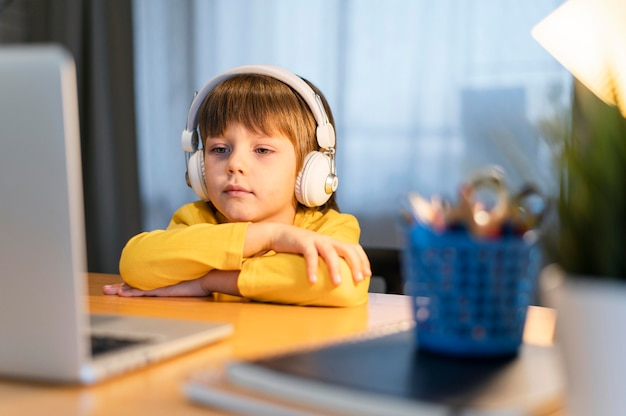 Garoto de escola com camisa amarela assistindo a uma aula virtual vista frontal Foto gratuita