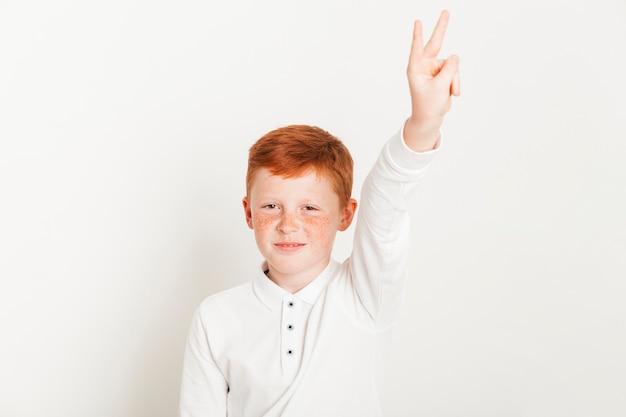 Garoto de gengibre mostrando dois dedos Foto gratuita