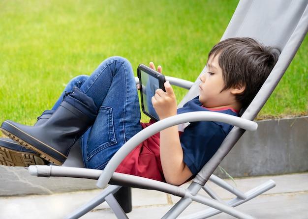 Garoto de retrato com o jogo no tablet, um garoto se divertindo assistindo desenhos animados no tablet digital, localização de criança na cadeira roacking relaxante no fim de semana no jardim na primavera ou verão Foto Premium