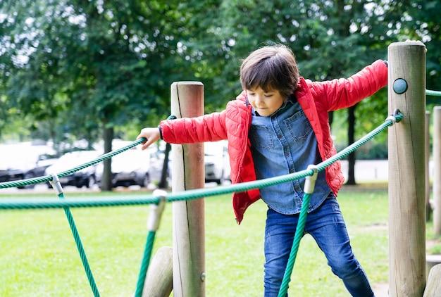Garoto de retrato subindo a corda no recreio Foto Premium