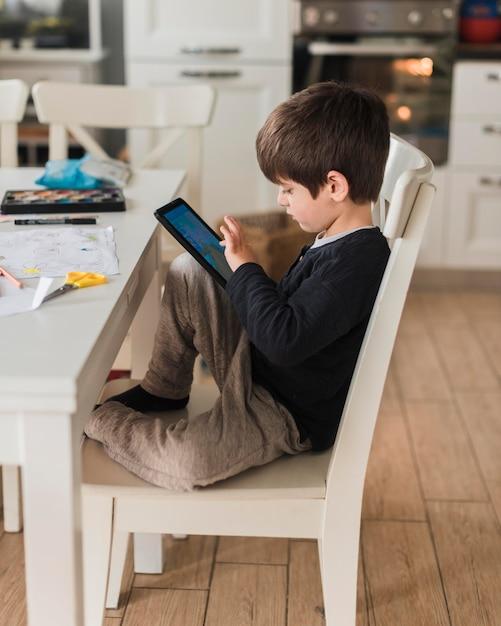 Garoto de tiro completo na cadeira com tablet Foto gratuita