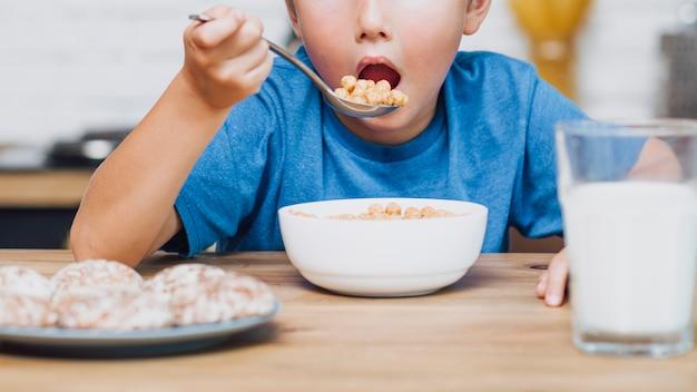Garoto de vista frontal comendo cereal Foto gratuita