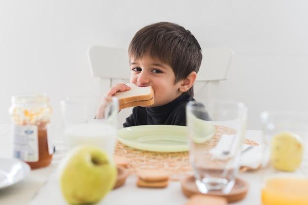 Garoto de vista frontal comendo sanduíche na mesa Foto gratuita