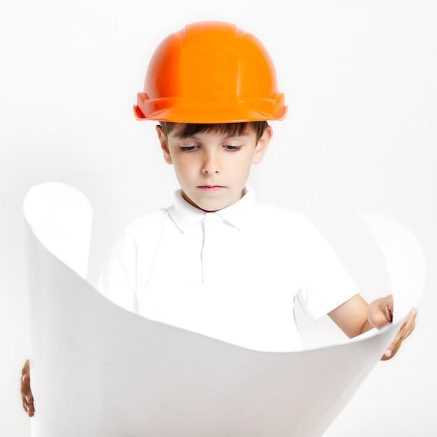 Garoto de vista frontal olhando planos de construções de introdução Foto gratuita