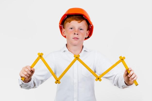Garoto de vista frontal posando como trabalhador da construção civil Foto gratuita