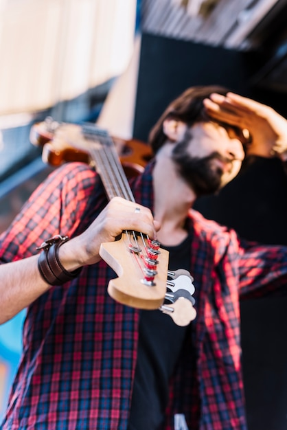 Garoto de vista inferior segurando a guitarra elétrica Foto gratuita