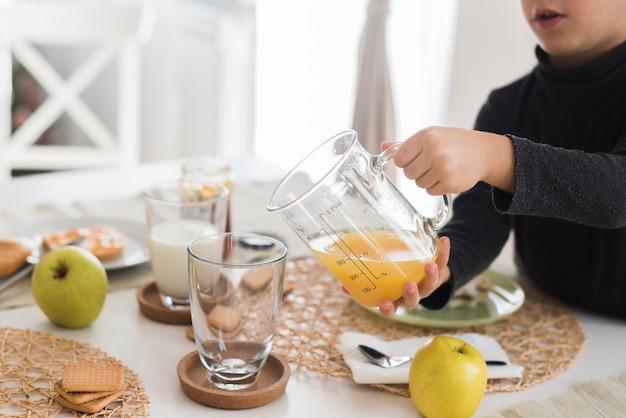 Garoto derramando suco de laranja em vidro Foto gratuita