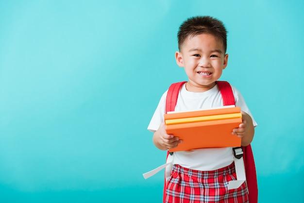Garoto do jardim de infância pré-escolar com livro e mochila Foto Premium