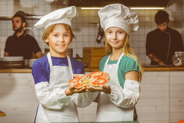 Garoto e garota chef felizes cozinhando na cozinha do restaurante Foto Premium