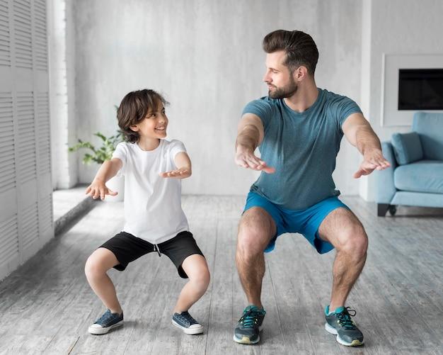 Garoto e seu pai fazendo esporte em casa Foto gratuita