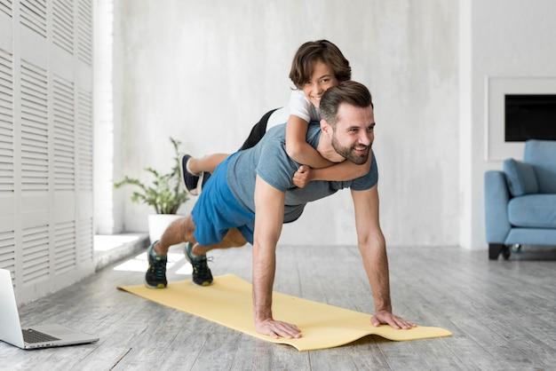 Garoto e seu pai fazendo esporte em casa Foto Premium