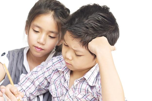 Garoto está fazendo lição de casa juntos sobre fundo branco Foto gratuita