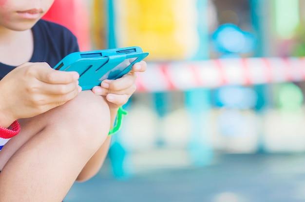 Garoto está jogando jogo no celular com fundo colorido Foto gratuita