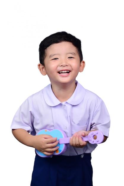 Garoto estudante asiática em uniforme escolar tocando o traçado de recorte de guitarra de brinquedo Foto Premium