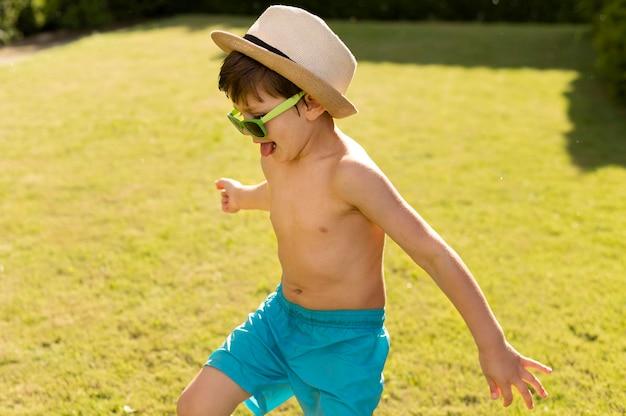 Garoto feliz com chapéu e óculos de sol Foto gratuita